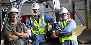 Workers standing near a truck in a workplace.