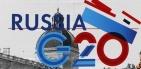 Une journaliste près de l'affiche du G20