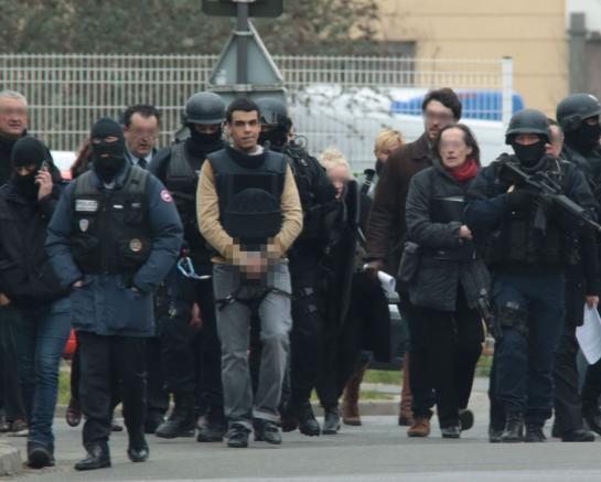 Villejuif (Val-de-Marne), le 20 mars 2016.Sid Ahmed Ghlam, protégé par un gilet pare-balles et encadré par des policiers lourdement armés, lors de la reconstitution du meurtre d'Aurélie Châtelain.