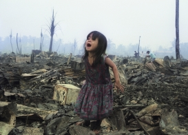 Girl cries at fire-ravaged home