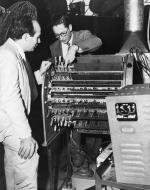 """J. Presper Eckert, Jr., co-designer and James R. Weiner, chief engineer, look over the new portable """"electronic brain."""""""