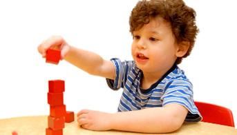Boy stacking blocks on a desk