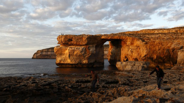 Tourists walk near the Azure Window, a 50 metre high rock arch, at Dwejra Point cliffs on the west coast of the Maltese island of Gozo November 13, 2009. Believed to have been formed millions of years ago, the arch is in danger of collapse due to natural erosion. REUTERS/Darrin Zammit Lupi (MALTA ENVIRONMENT TRAVEL) MALTA OUT. NO COMMERCIAL OR EDITORIAL SALES IN MALTA
