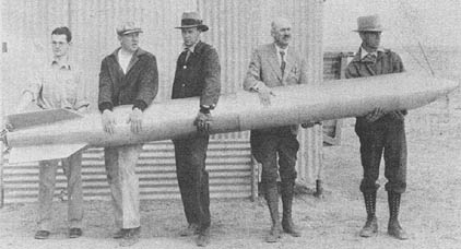 Dr. Robert H. Goddard {second from right) and his colleagues holding a liquid-propellant rocket in 1932 at their New Mexico workshop.