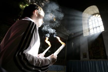 Un pèlerin priait et brûlait de l'encens, hier,... (Photo: Reuters)