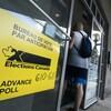 Un homme entre dans un bureau de vote. On le voit de dos. Au premier plan, une pancarte jaune sur laquelle est écrit « Bureau de vote par anticipation, Élections Canada ».