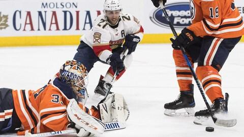 Vincent Trocheck des Panthers tente de s'emparer d'un retour de lancer, non contrôlé par le gardien des Oilers, Cam Talbot.
