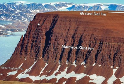 large brown mountain with flat top against backdrop of snow covered mountains
