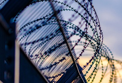 barbed wire circles a fence against backdrop of blue sky and sunrise