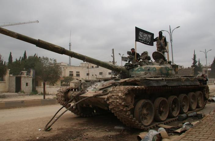 Fighters from a coalition of Islamist forces stand on a tank on March 29, 2015 in the Syrian city of Idlib, the second provincial capital to fall from government control (AFP Photo/Zein al-Rifai)