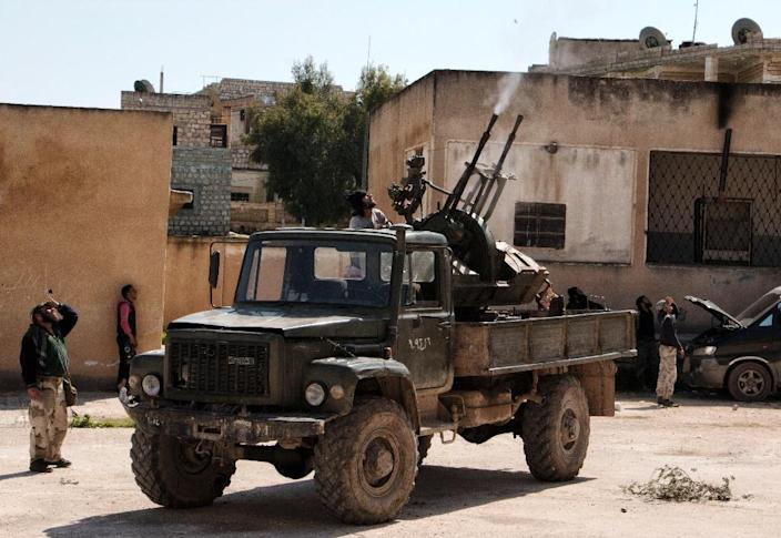 Rebel fighters fire an anti-aircraft machine gun mounted on a vehicle deploy in the northwestern Syrian city of Idlib on March 26, 2015 (AFP Photo/Karam al-Masri)
