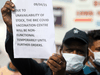 A guard holds up a notice to inform people about the shortage of COVID-19)vaccine supplies at a vaccination centre, in Mumbai, India.