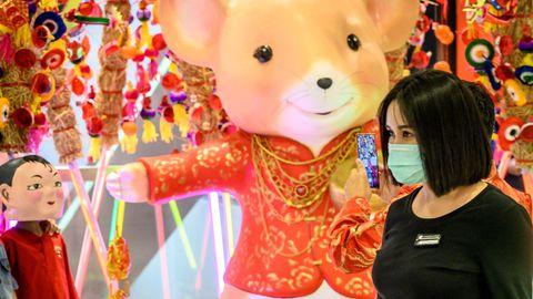 Une femme porte un masque de protection contre le nouveau coronavirus dans un magasin décoré pour le Nouvel An chinois à Bangkok le 24 janvier 2020