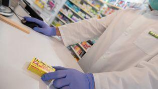 Un pharmacien vend une boîte de Doliprane, le 24 mars 2020 à Excideuil (Dordogne). (ROMAIN LONGIERAS / HANS LUCAS / AFP)