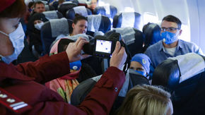 An official uses a thermal imaging device to measure the temperatures of passengers on an airplane