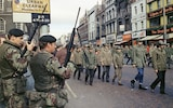 """FILE - In this Aug. 1972 file photo British troops watch as members of the Ulster Defence Association parade through Belfast, Northern Ireland. The chaotic scenes during a week of violence on the streets of Northern Ireland have stirred memories of decades of Catholic-Protestant conflict, known as """"The Troubles."""" A 1998 peace deal ended large-scale violence but did not resolve Northern Ireland's deep-rooted tensions. (AP Photo, File)"""