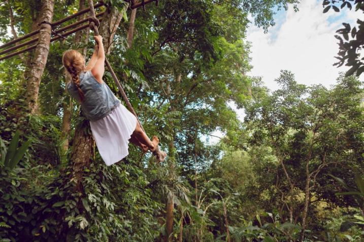 Une fille se balance sur un arbre, dans une forêt.
